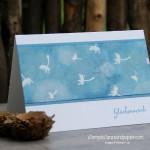 Eine Karte in Aquarell- und Bokehtechnik mit embossten Pusteblumen
